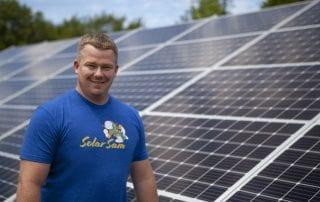 Ches Headshot of Solar Sam with Solar Panel Array Installation Behind. Servicing both Missouri Illinois Solar Panel Needs